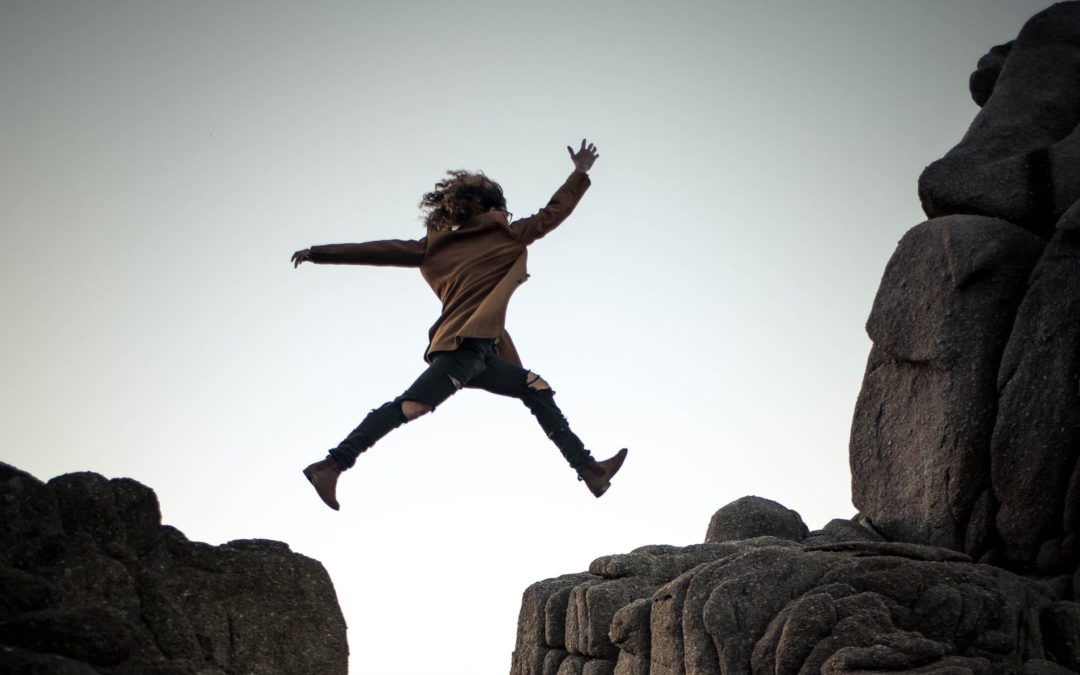 Frau springt über Felsen